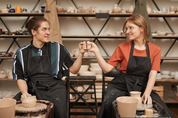 Front view portrait of two young artisans bumping fists while making ceramics in pottery workshop with pottery wheel, copy space