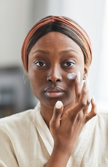 Front view portrait of young african-american woman using face cream or moisturizer, skincare and beauty routine concept