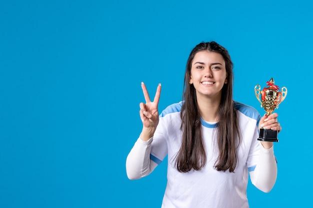 Vista frontale che posa giocatore femminile con la tazza sull'azzurro