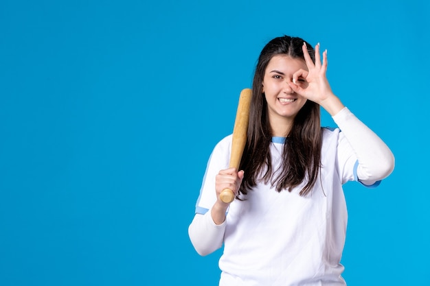 青の野球のバットで若い女性のポーズの正面図