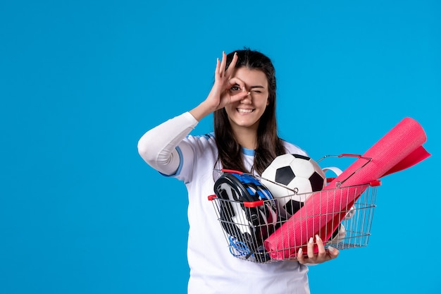 Front view posing young female with basket full of sport things blue