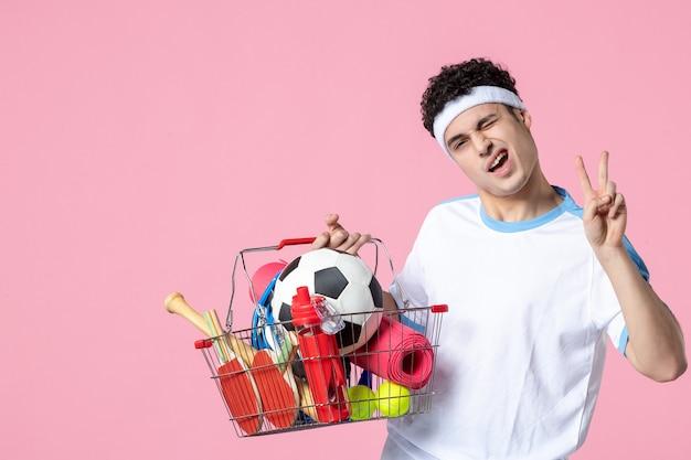 スポーツ物でいっぱいのバスケットとスポーツ服で若い男性のポーズを正面から見た図