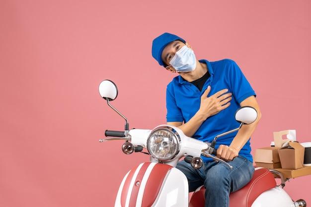 Vista frontale dell'uomo corriere positivo in maschera medica che indossa cappello seduto su scooter su sfondo pesca pastello