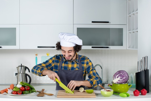 Vista frontale dello chef maschio positivo con verdure fresche e cucinare con utensili da cucina e tagliare peperoni verdi nella cucina bianca white