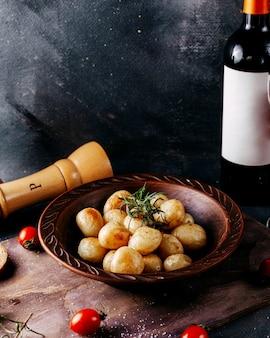 Картофель спереди обжаренный немного вместе с красными помидорами и красным вином на серой поверхности