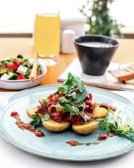 Вид спереди картофель с мясом в томатном соусе с рукколой и греческим салатом на столе