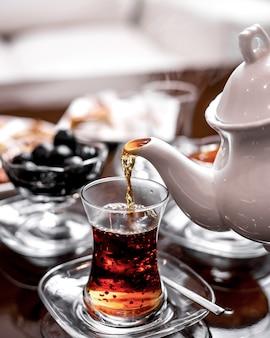 Vista frontale versa il tè in un bicchiere di armudu da un bollitore