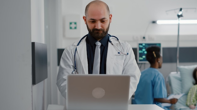 Front view of practitioner doctor typing illness expertise on computer while in background black nurse discussing healthcare treatment. hospitalized patient having respiratory disorder