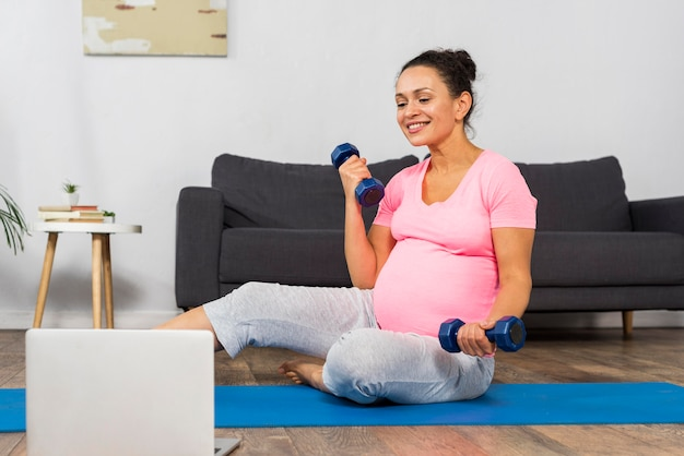 Vista frontale della donna incinta a casa che si esercita sulla stuoia con laptop e pesi