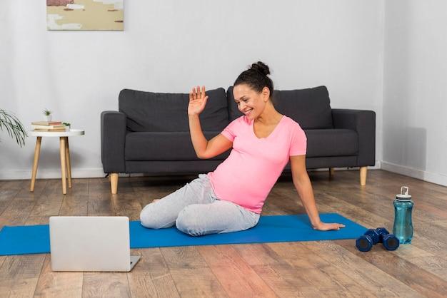 Vista frontale della donna incinta a casa che esercitano sulla stuoia con il computer portatile