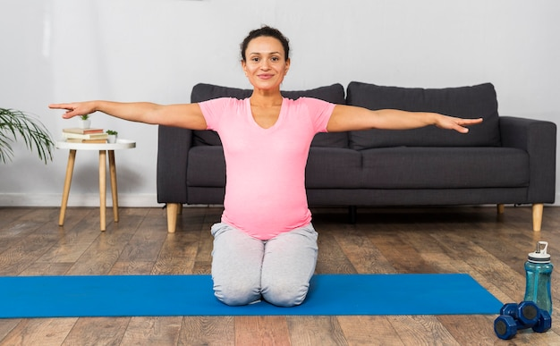 Front view of pregnant woman at home exercising on mat