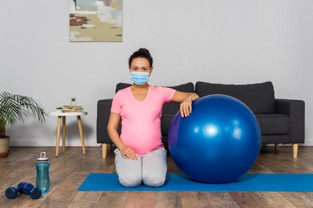 Vista frontale della donna incinta a casa con maschera medica e palla ginnica