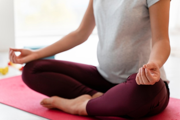 Вид спереди беременная женщина, медитирующая в гостиной