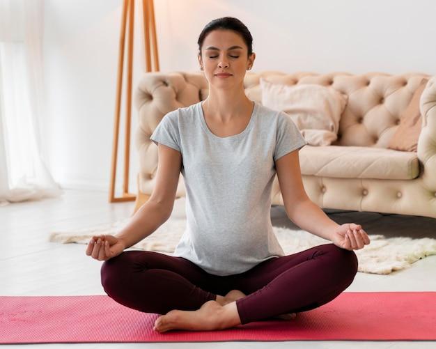 Вид спереди беременная женщина медитирует