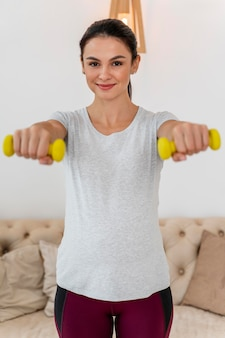 黄色の重みでトレーニングする正面図妊娠中の女性
