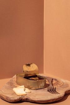 Vista frontale cibo conservato in lattina con forchetta e pane tostato