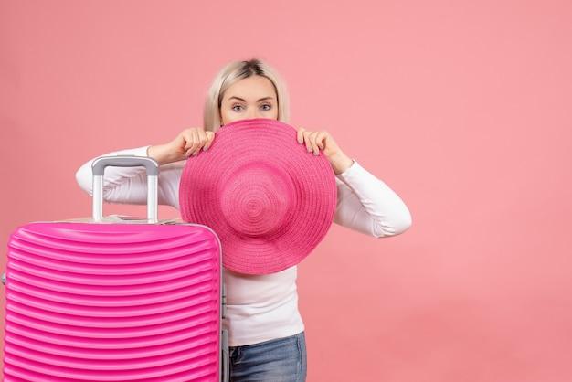 Vista frontale bella donna bionda in piedi vicino alla valigia mettendo il cappello di panama davanti al viso