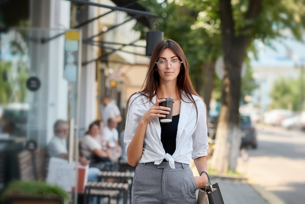 Front view of pretty brunette walking in downtown drinking coffee.