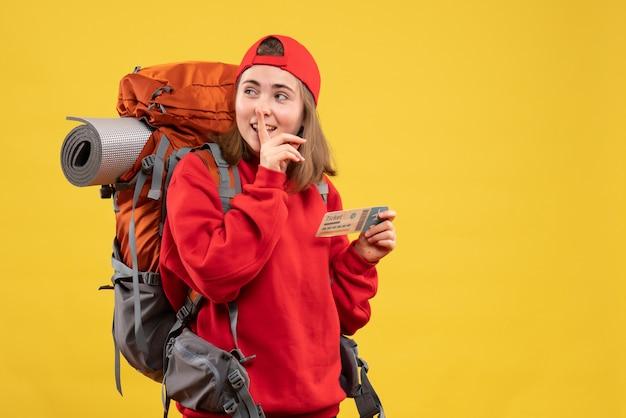 Вид спереди симпатичная женщина-турист с рюкзаком, держащим билет на самолет, делая знак тишины