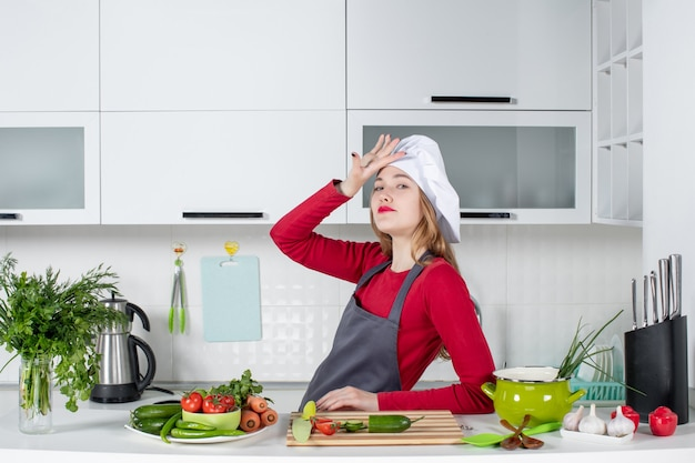Front view pretty female chef in cook hat standing in kitchen
