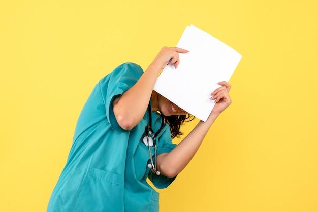 Vista frontale del medico femminile grazioso che copre il viso con documenti sulla parete gialla