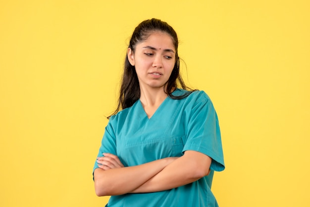Vista frontale del medico femminile grazioso che attraversa le mani sulla parete gialla