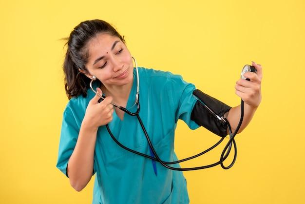 黄色の背景に血圧測定装置を使用して制服を着たきれいな女性医師の正面図