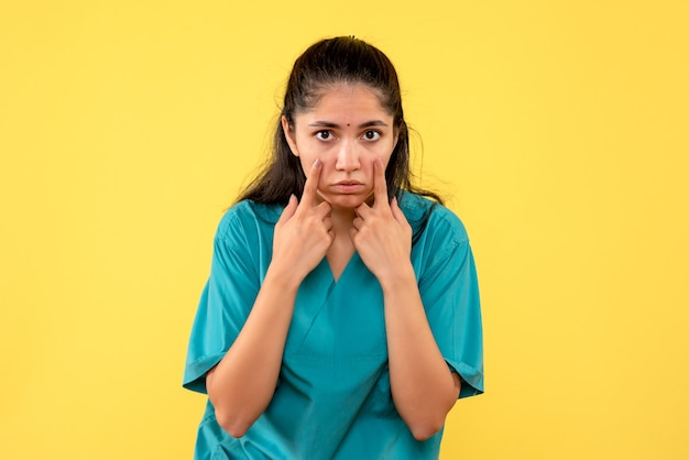 Vista frontale del medico femminile grazioso che indica i suoi occhi sulla parete gialla