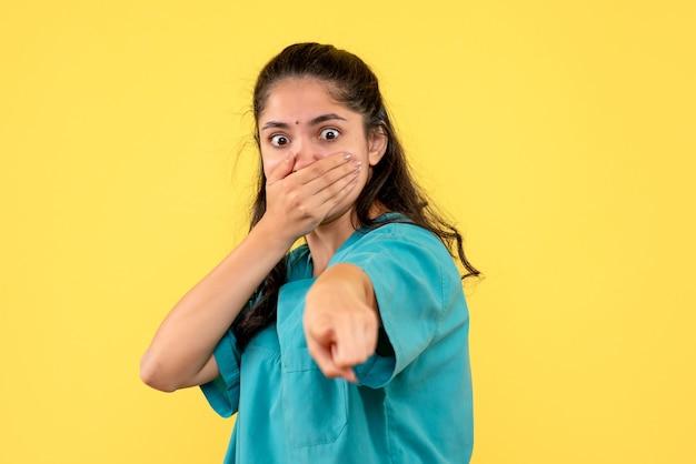 Vista frontale del medico femminile grazioso che mette la mano sulla sua bocca che indica qualcosa sulla parete gialla