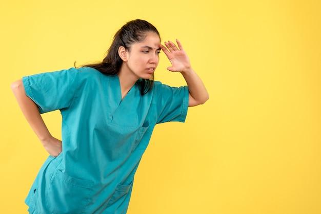 Vista frontale del medico femminile grazioso che mette la mano su una vita sulla parete gialla