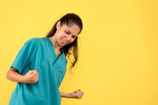 Vista frontale del medico femminile grazioso che mostra il gesto vincente sulla parete gialla