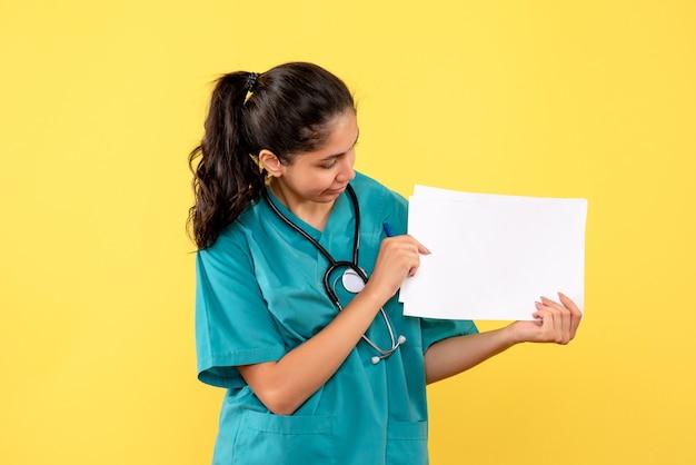 Vista frontale della bella dottoressa in uniforme guardando i documenti sulla parete gialla