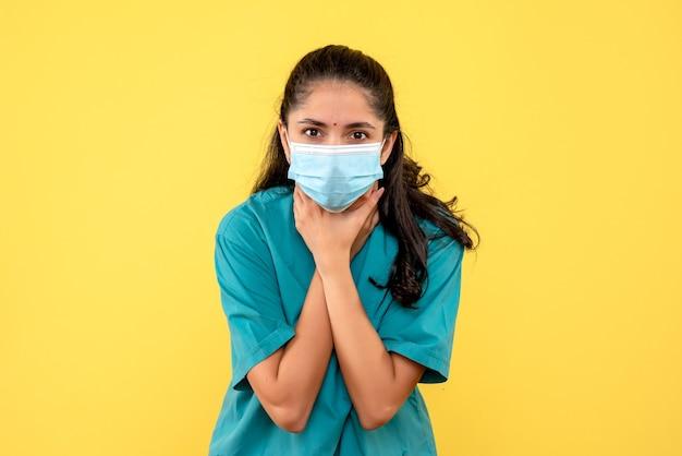Vista frontale del medico femminile grazioso con mascherina medica che tiene la sua gola sulla parete gialla