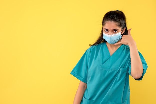 Vista frontale del medico femminile grazioso con mascherina medica che mi chiama segno sulla parete gialla