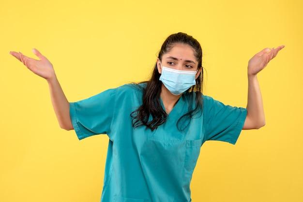 Vista frontale del medico femminile grazioso con mascherina medica che apre le sue mani sulla parete gialla
