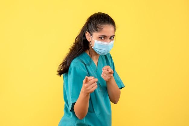 Vista frontale del medico femminile grazioso con la mascherina medica pointign nella parte anteriore sulla parete gialla