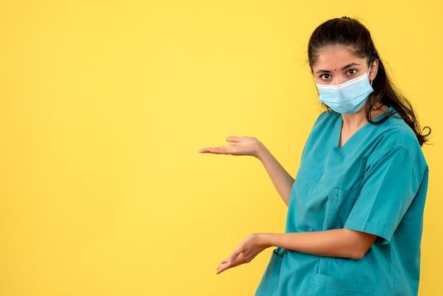 Vista frontale del medico femminile grazioso con la mascherina medica che punta a qualcosa sulla parete gialla