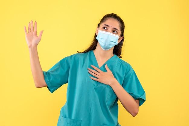 Vista frontale della bella donna medico con maschera medica promettente sulla parete gialla