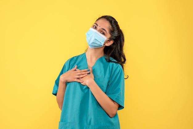 Vista frontale del medico femminile grazioso con mascherina medica che mette la mano su una cassa sulla parete gialla