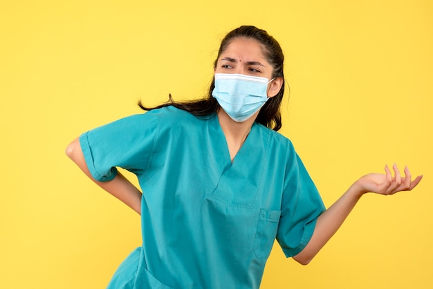 Vista frontale del medico femminile grazioso con mascherina medica che mette la mano su una vita sulla parete gialla