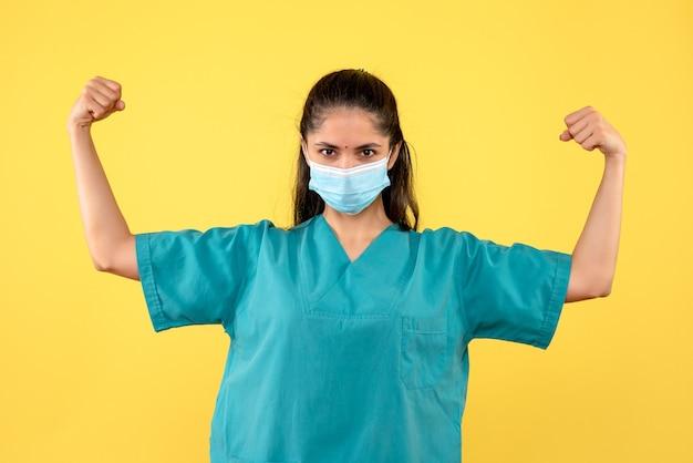 Vista frontale del medico femminile grazioso con mascherina medica che mostra i muscoli sulla parete gialla