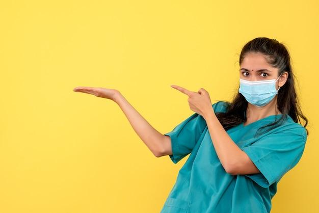 Vista frontale della bella donna medico con mascherina medica sulla parete gialla