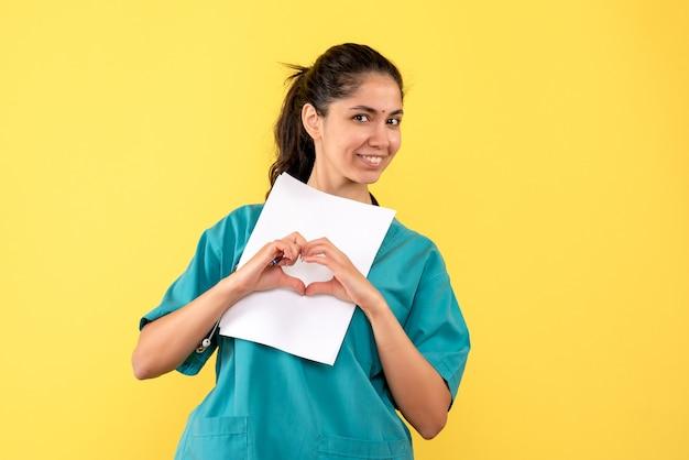 Vista frontale del medico femminile grazioso con documenti che fanno il segno del cuore con le mani sulla parete gialla