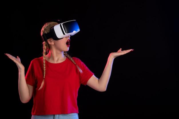 Vista frontale di una bella donna che gioca con eccitazione vr su un buio giochi fantasy ad ultrasuoni d