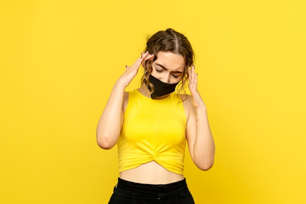 Front view of pretty female having headache on yellow