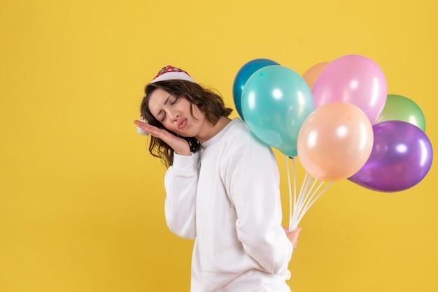 Vista frontale bella femmina nascondendo palloncini colorati su giallo