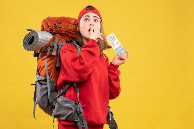 Vista frontale bella femmina escursionista con zaino in possesso di biglietto aereo facendo segno di silenzio
