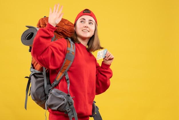 Vista frontale piuttosto femmina escursionista con zaino che tiene biglietto aereo agitando la mano