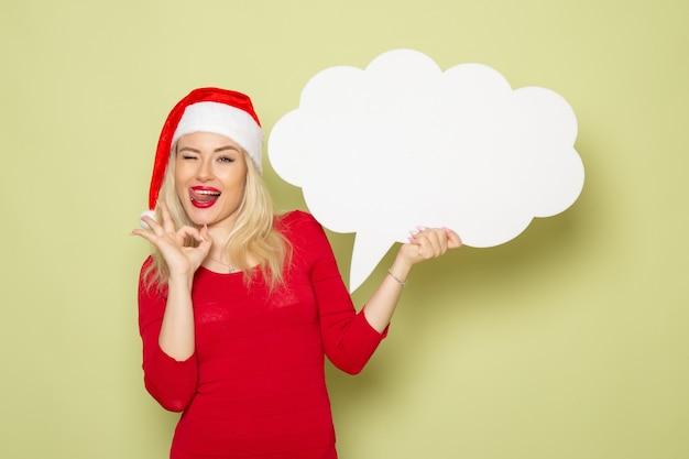Donna graziosa di vista frontale che tiene grande segno bianco sulla parete verde natale neve foto vacanze emozioni anno nuovo