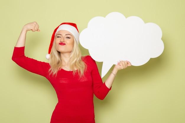 Vista frontale bella femmina con grande cartello bianco sulla parete verde natale neve foto vacanze emozione capodanno